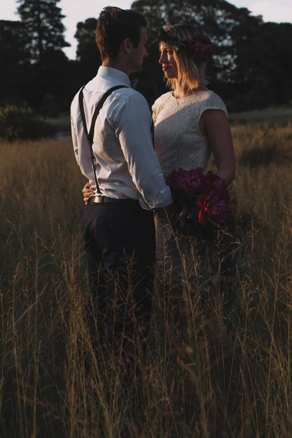 bride and groom standing in long grass on sunset